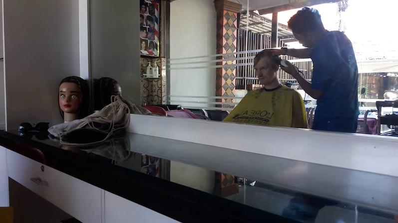 Nach Kanada, Guatemala und Japan, wollte Bernd auch den balinesischen Friseur austesten, man achte auf die gruselige Puppe im Hintergrund; Sanur, Bali | wat-erleben